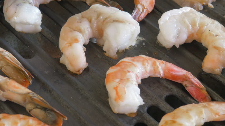 Closeup of shrimp cooking on a grill in 4k. The shellfish cooks on a searing hot cast iron grate. Authentic shot could be used in videos on cooking, travelogues, food allergies and global overfishing. Royalty-Free Stock Footage #1020475810