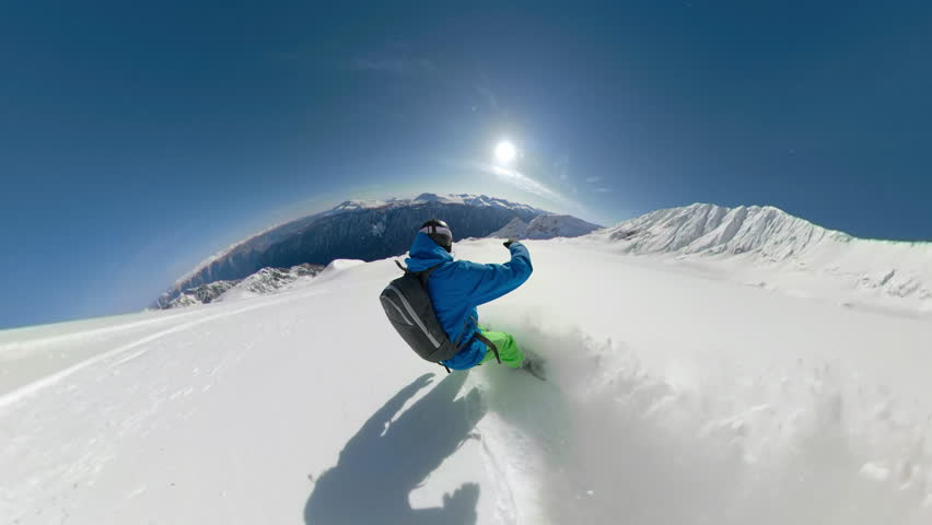 FOLLOW: Extreme freeride snowboarder shredding pristine snow in remote mountain terrain. Snowboarder heliskiing fresh powder snow high in the sunny mountains. Pro rider heliboarding off piste slopes