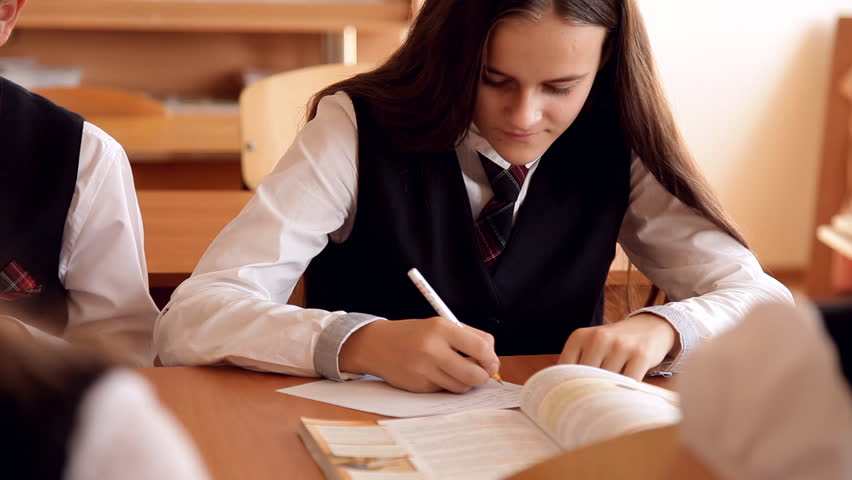 the girl withdraws on the lesson and the teacher closes the book Royalty-Free Stock Footage #1020500017