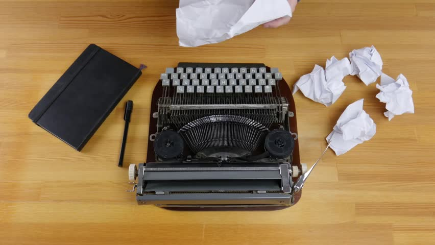 Typewriter, notebook and crumpled sheets of paper on a wooden table. Male hands hold a piece of paper and then throw it away. | Shutterstock HD Video #1020505696