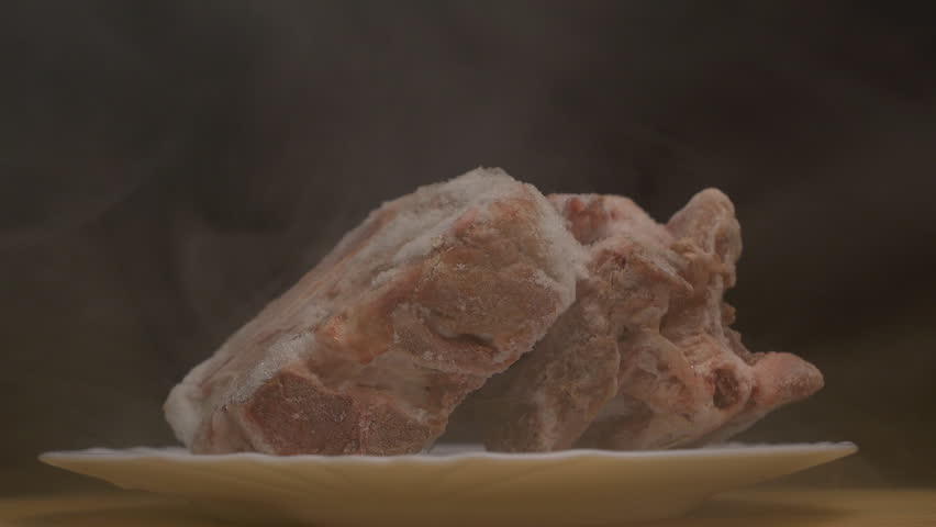 Pieces of frozen rotating meat on a black background, from which blows frosty freshness and cold, smoke, close-up, slow motion, copy space   Shutterstock HD Video #1020515128