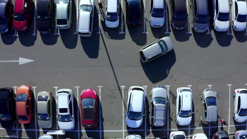 Top view car driving on parking place. Aerial view from above flying drone car moving and standing on parking lot in modern city. Car traffic and parking concept