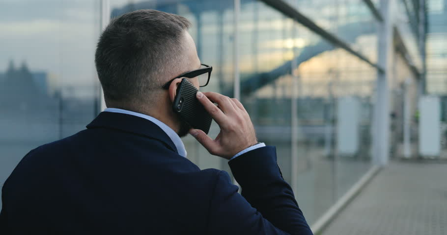 Back view on the Caucasian businessman in glasses walking the street at the office center and talking on the phone. Close up. Rear. Outside. Royalty-Free Stock Footage #1020518893