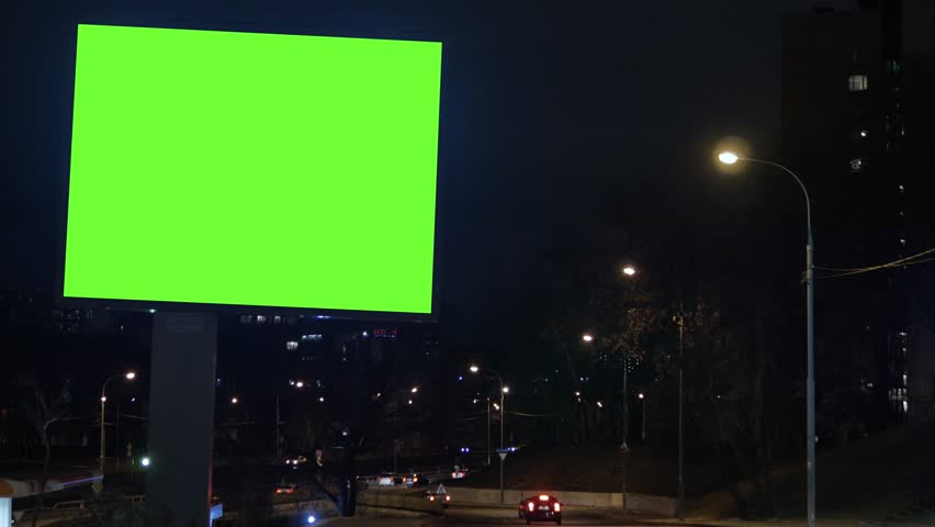 Billboard with a green screen, located on a busy street. Cars move in the evening. | Shutterstock HD Video #1020521011