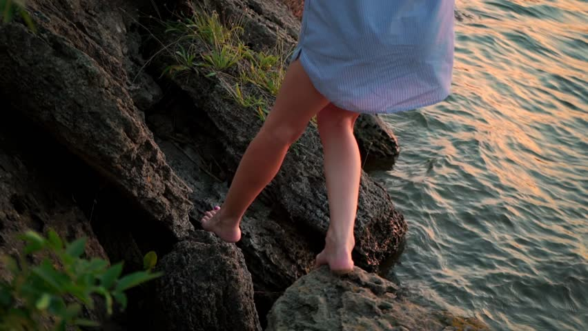 A young woman walks on the rocks by the sea. Barefoot woman in a light shirt goes near the lake. Ocean coast, bay. Summer holidays on the island. Time to think. Fresh air. Freedom. Revelation. #1020523063