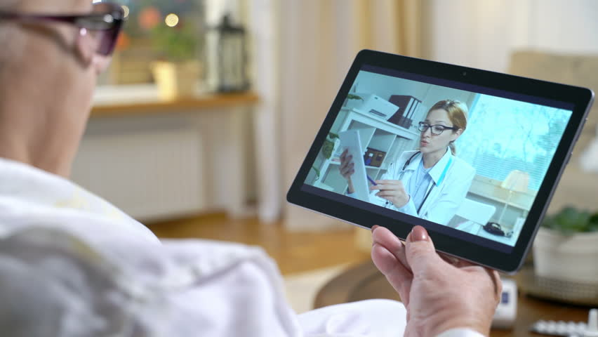 Medicine online. Home quarantine coronavirus. Elderly woman is consulting with female doctor using video chat at home. The doctor showing her the results of medical tests