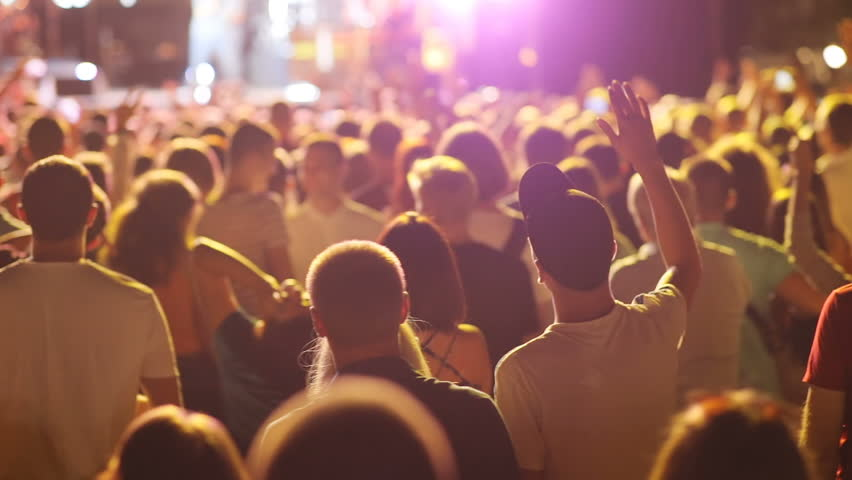 Young people enjoying music at concert, dancing. Evening in city, outdoors. Crowd of fans. Moment, outdoors. Favorite rock band. #1020531238