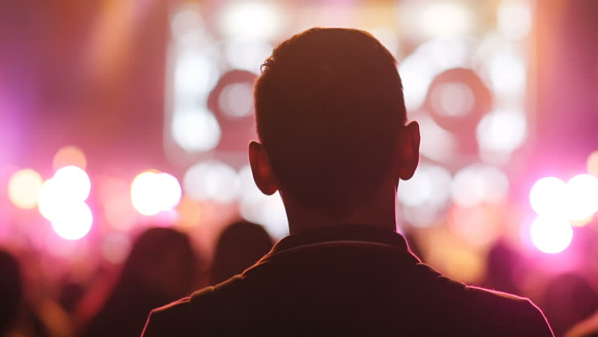 Close-up back of young man looking forward. Silhouette of concert crowd, backstage. Night, flashes, lights.