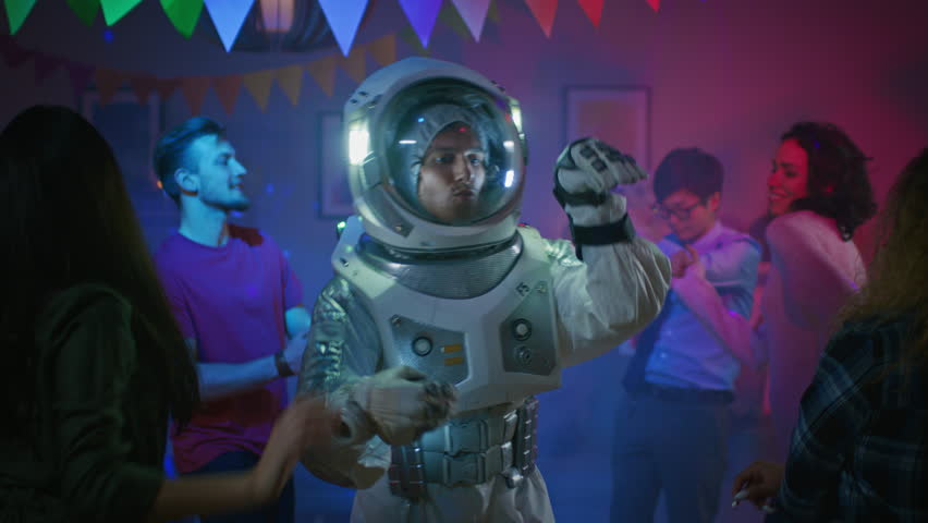 At the College House Costume Party: Fun Guy Wearing Space Suit Dances Off, Doing Groovy Funky Robot Dance Modern Moves. With Him Beautiful Girls and Boys Dancing in Neon Lights. In Slow Motion. #1020543019