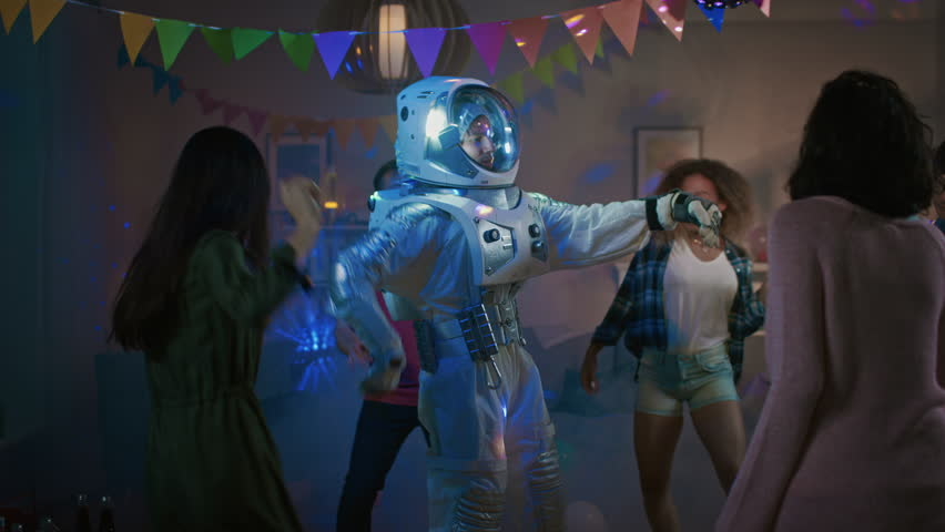 At the College House Costume Party: Fun Guy Wearing Space Suit Dances Off, Doing Robot Dance Modern Moves. With Him Beautiful Girls and Boys Dancing in Neon Lights. #1020543025