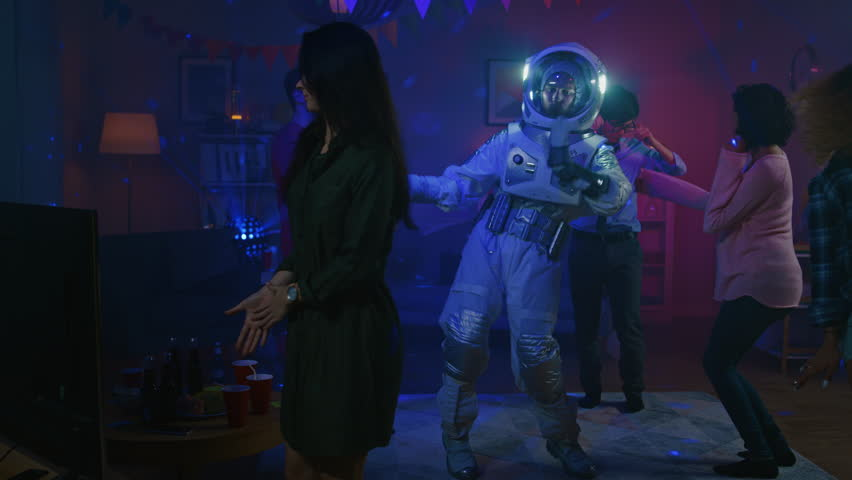 At the College House Costume Party: Fun Guy Wearing Space Suit Dances Off, Doing Groovy Funky Robot Dance Modern Moves. With Him Beautiful Girls and Boys Dancing in Neon Lights. #1020544111