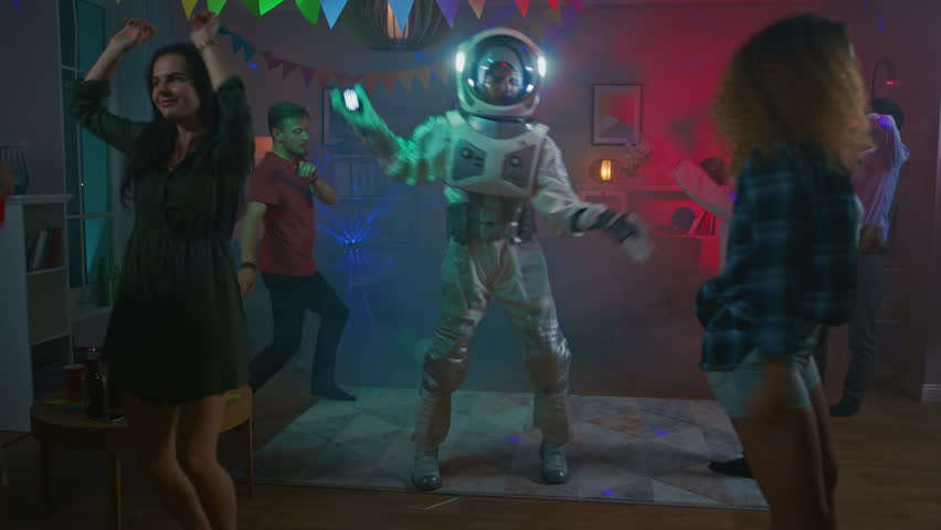 At the College House Costume Party: Fun Guy Wearing Space Suit Dances Off, Doing Groovy Funky Robot Dance Modern Moves. With Him Beautiful Girls and Boys Dancing in Neon Lights. #1020544114