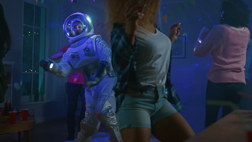 At the College House Costume Party: Fun Guy Wearing Space Suit Dances Off, Doing Groovy Funky Robot Dance Modern Moves. With Him Beautiful Girls and Boys Dancing in Neon Lights. #1020544117