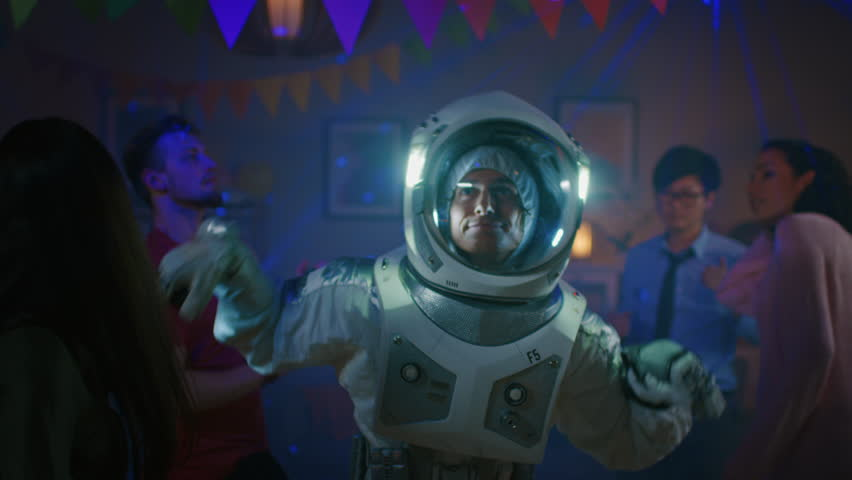 At the College House Costume Party: Fun Guy Wearing Space Suit Dances Off, Doing Groovy Funky Robot Dance Modern Moves. With Him Beautiful Girls and Boys Dancing in Neon Lights. | Shutterstock HD Video #1020544129