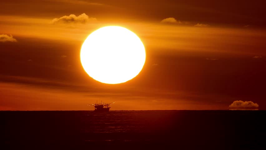 Sunset is a fishing boat running under the sun. #1020547924
