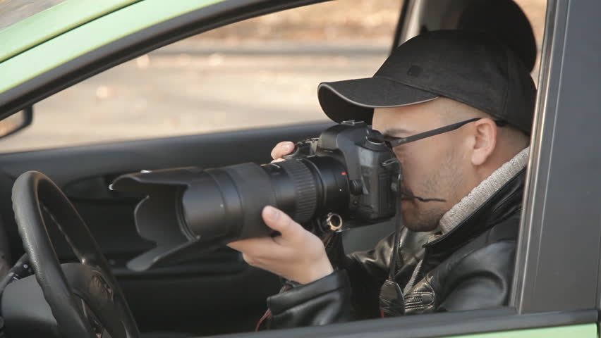 A private detective or a spy conducts surveillance of the object of surveillance. A man secretly taking pictures from the car window