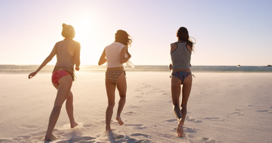 Young women running into ocean at sunset in slow motion taking off clothes on tropical beach | Shutterstock HD Video #10205780
