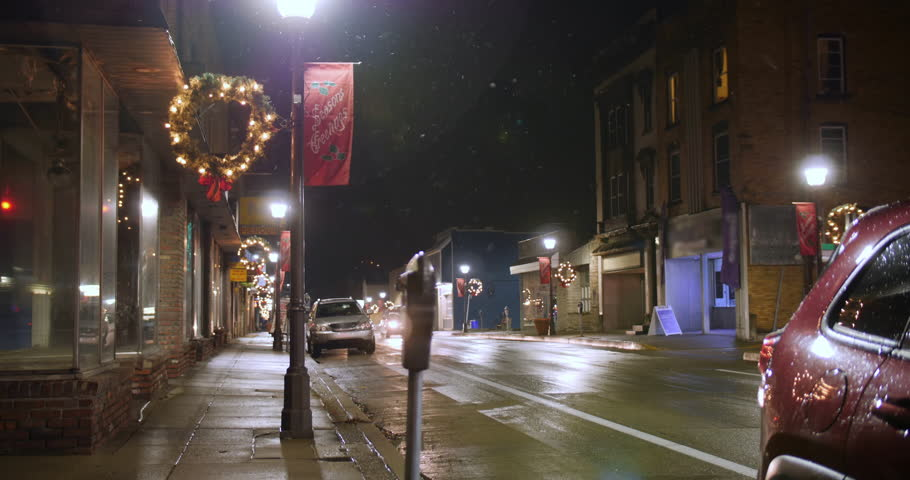 A nighttime view of traffic passing businesses on a typical American main street during Christmas. Pittsburgh suburbs.