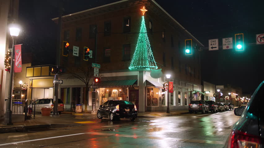 A nighttime establishing shot of a typical street corner in the business district of a small town during Christmas season. Pittsburgh suburbs. Additional rights may be needed for commercial use.   Shutterstock HD Video #1020589168