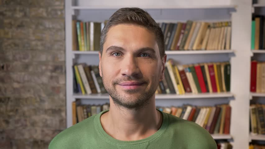 Adult man looking forward, smiling and blinking calmly. Bookshelves on the background | Shutterstock HD Video #1020589888