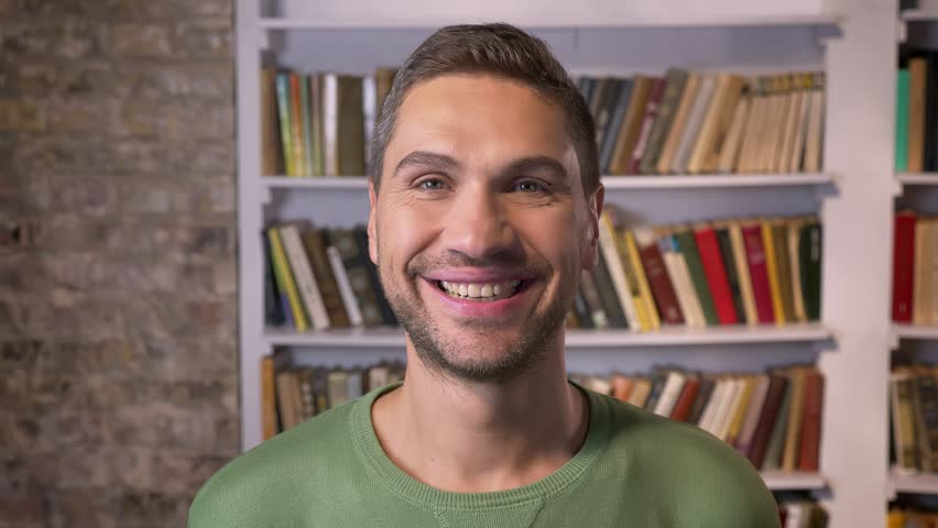 Adult man looking forward, widely smiles. Bookshelves on the background | Shutterstock HD Video #1020589897