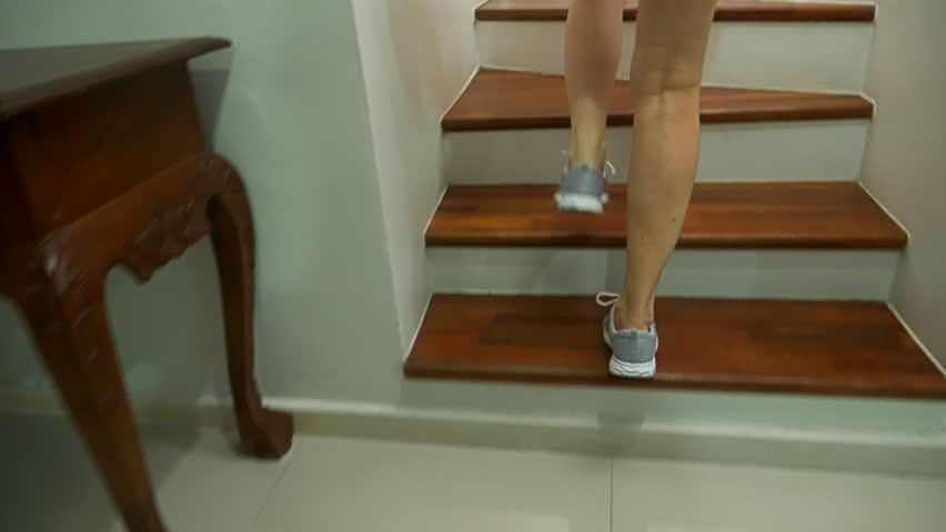 Female legs in sneakers running along a wooden ladder
