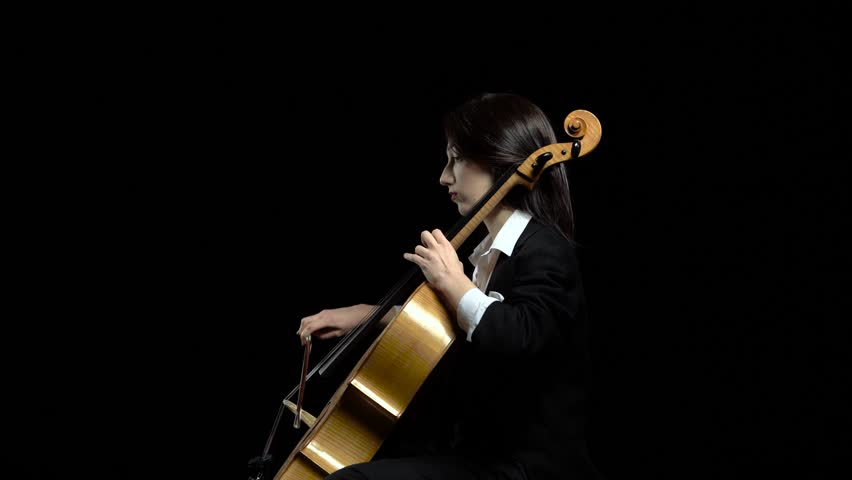 Female hand plays with a bow on a cello in dark studio . Black background. Side view #1020610027
