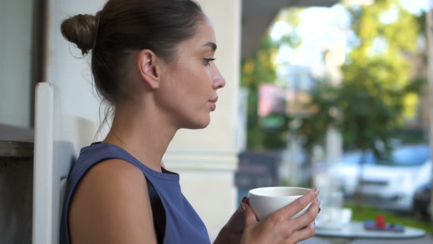 Beautiful brunette girl relaxing outside coffee shop in bright summer day enjoying her morning coffee. Slow motion | Shutterstock HD Video #1020611050
