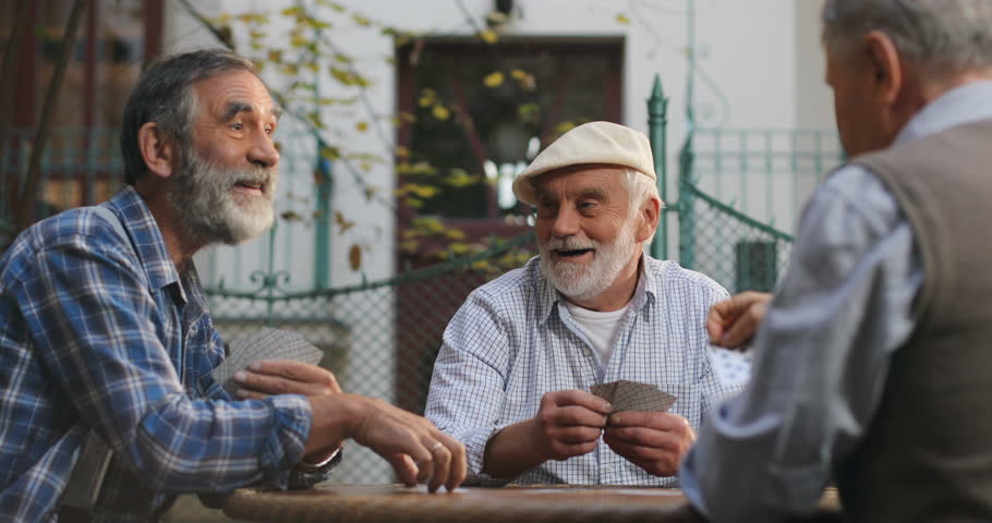 Portrait shot of the Caucasian senior man sitting at the table outdoors in the yard, playing cards game and talking.