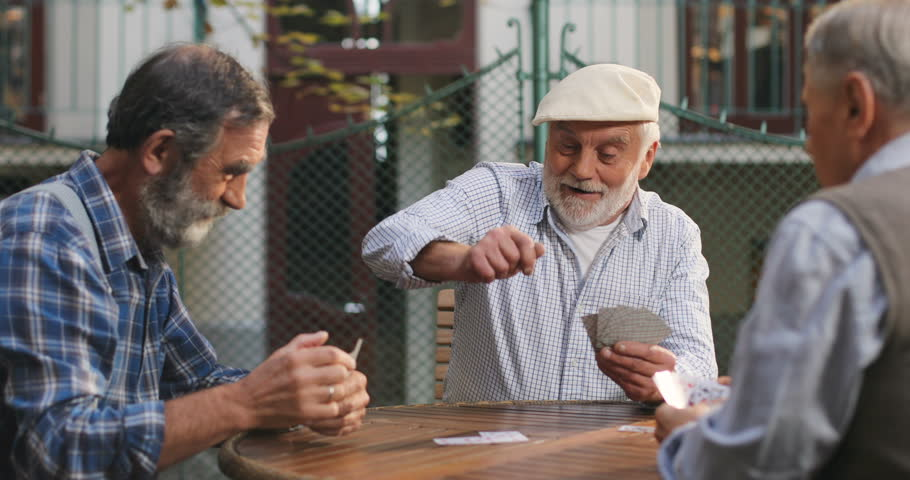 Three Caucasian senior men best friends on retirement playing cards in the yard at the table. Outside.