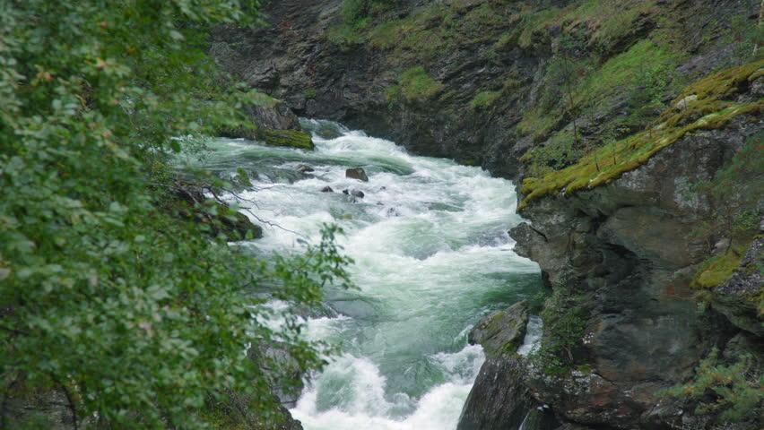 Raging water flowing down between rocks in mountains in Norway #1020620017