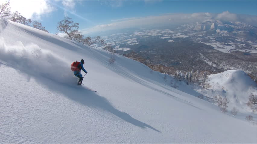 SLOW MOTION, DRONE: Awesome freestyle skier shredding the fresh snow while riding in the scenic mountains in Japan. Flying along the active male tourist skiing downhill in the breathtaking backcountry