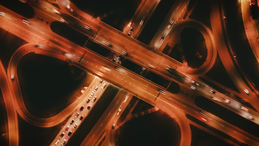Highway cloverleaf interchange intersection (junction) with ramps, heavy traffic, aerial hyperlapse. A cloverleaf typical  two-level, four-way interchange.