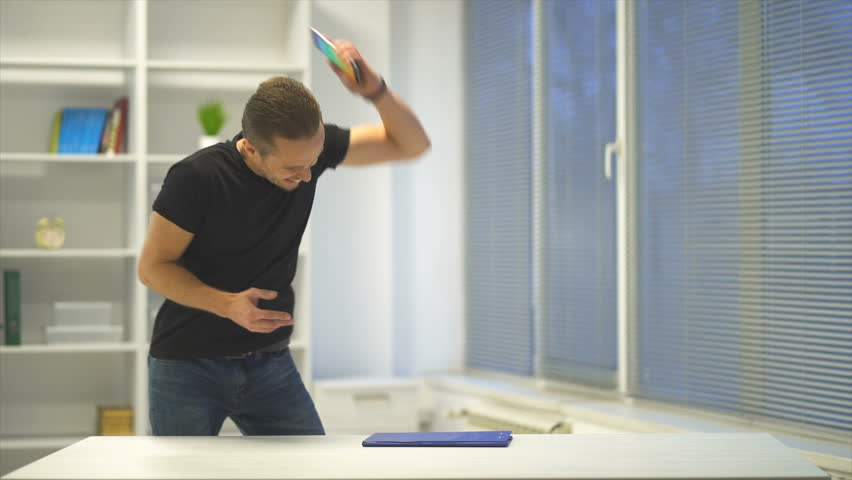 The angry man throws the phone on the table. slow motion | Shutterstock HD Video #1020658714