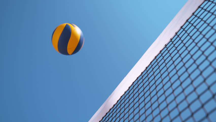 SLOW MOTION, CLOSE UP, LOW ANGLE: Unknown beach volleyball player smashes the ball past the blocker's arms and hands. Cool shot of unknown athletic people playing volleyball on a sunny summer day.