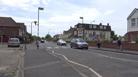 CLACTON-ON-SEA, ESSEX, ENGLAND - 1ST JUNE 2015: Cars drive along a road and cross a pedestrian crossing in an English suburb.