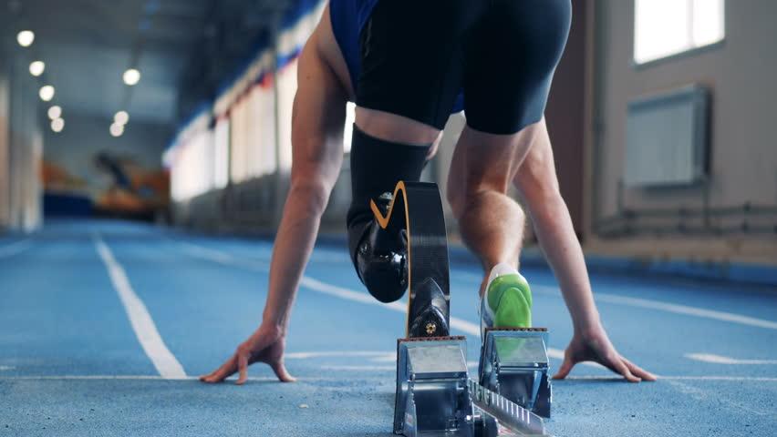 A man sprints, wearing prosthetic leg, back view.