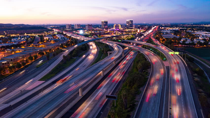 Aerial hyperlapse drone shot of fast moving freeway traffic at night showing cars and light streaks | Shutterstock HD Video #1020718630