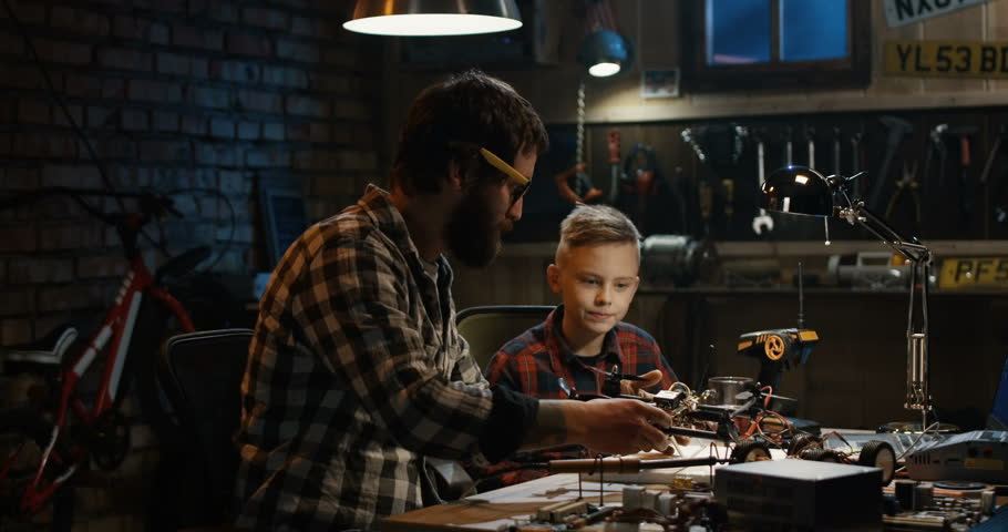 Medium shot of a father and son repairing a drone in a garage | Shutterstock HD Video #1020729574
