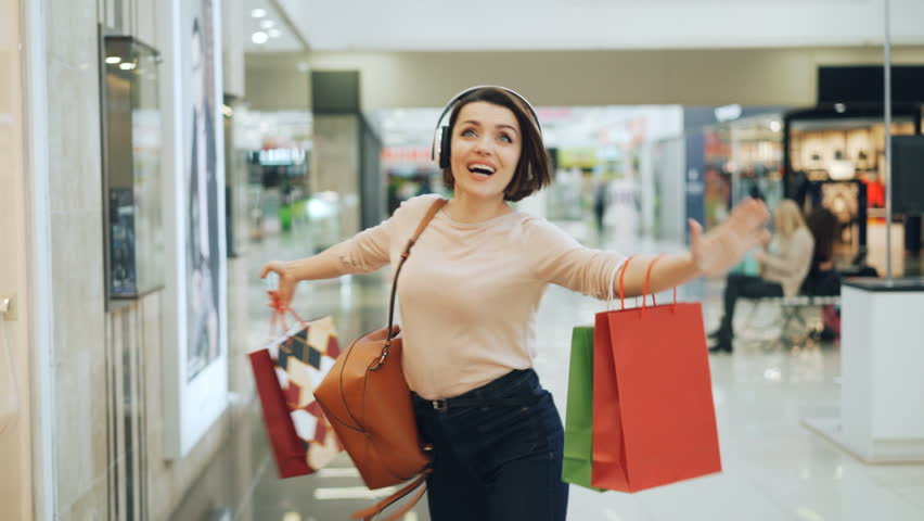 Happy female shopaholic is having fun in shopping mall listening to music in headphones, dancing with bright bags and laughing pointing at goods in shop windows. Royalty-Free Stock Footage #1020738268