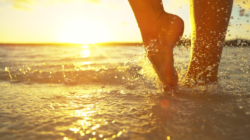 SLOW MOTION, CLOSE UP, LENS FLARE: Unrecognizable carefree woman enjoying a relaxing walk in the refreshing ocean water on a beautiful summer morning. Glassy drops of water splash around girl's feet. #1020743173