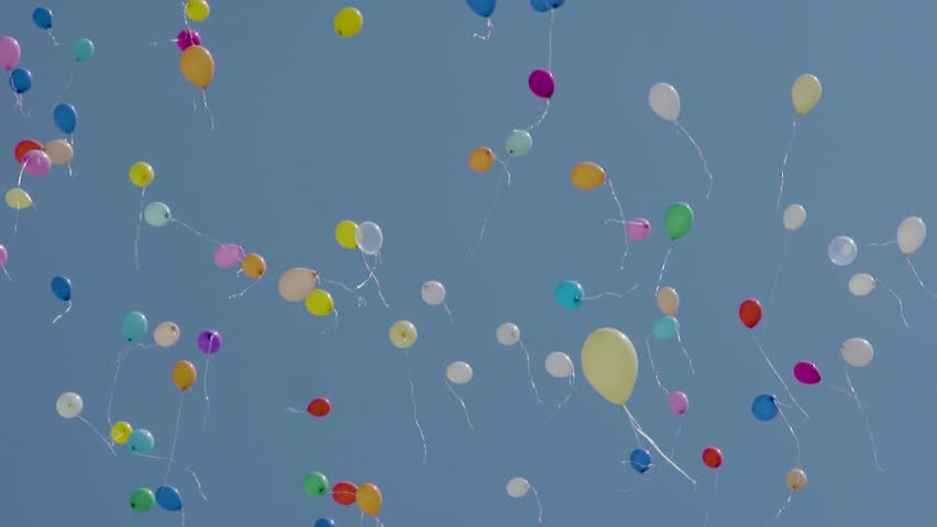 Colorful helium balloons floating against a blue sky. Slow motion