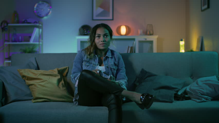 Beautiful Excited Young Black Gamer Girl Sitting on a Couch and Playing Video Games on a Console. She Plays with a Wireless Controller. Cozy Room is Lit with Warm and Neon Light. | Shutterstock HD Video #1020758110