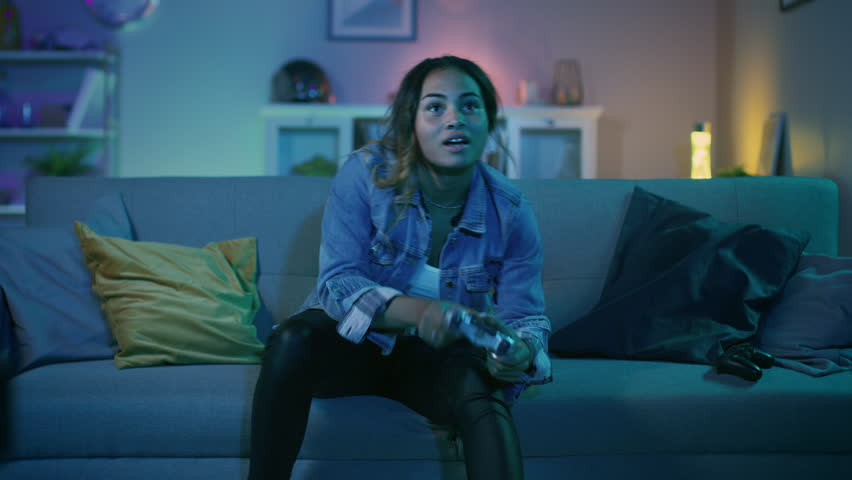 Beautiful Excited Young Black Gamer Girl Sitting on a Couch, Playing and Winning in Video Games on a Console. She Plays with a Wireless Controller. Cozy Room is Lit with Warm and Neon Light. | Shutterstock HD Video #1020758131