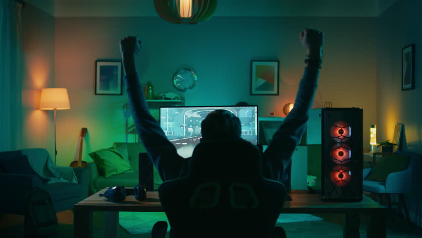 Back Shot of a Gamer Playing and Winning in First-Person Shooter Online Video Game on His Powerful Personal Computer. Room and PC have Colorful Neon Led Lights. Cozy Evening at Home. #1020758392