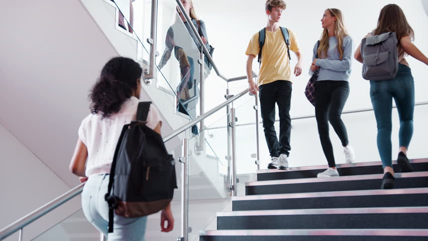 High School Students And Staff Walking On Stairs Between Lessons In Busy College Building