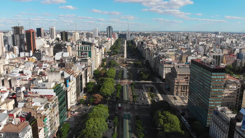 Panoramic Aerial drone view of Buenos Aires obelisk on avenida de Julio in Buenos Aires, Argentina. Shows buildings and skyscrapers with car traffic in the Street below.