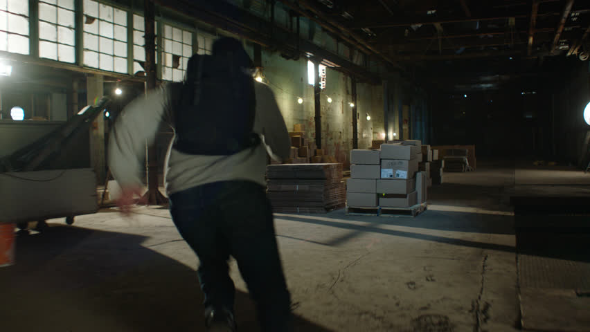 African american man runs from a caucasian man as both perform parkour over crates and boxes in a dark warehouse, in moody lighting. Medium shot in 4K with an Alexa Mini camera