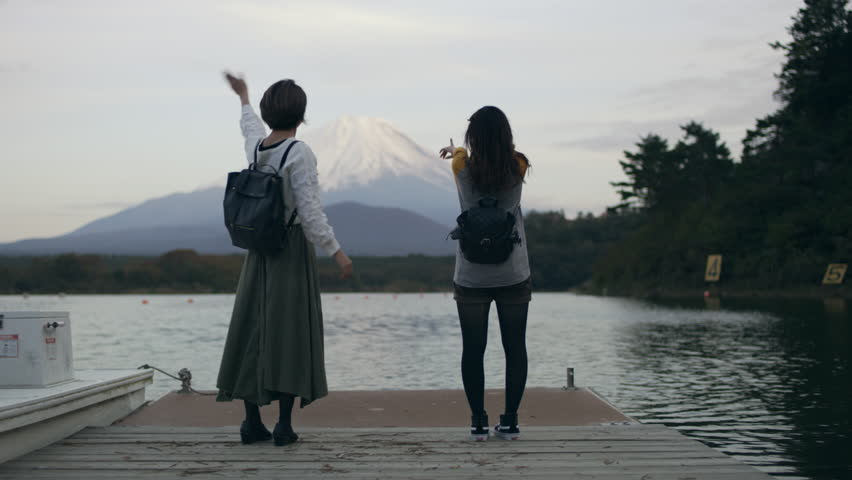 Medium shot on 4k RED camera. Excited Japanese women running up a dock on the water to see Mount Fuji and happily waving at it with soft natural lighting.