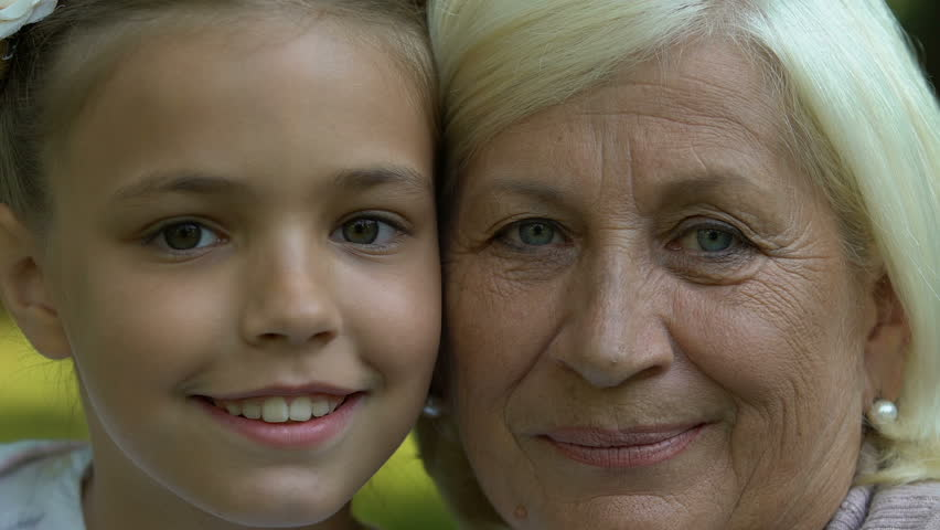 Grandmother and granddaughter looking in camera, generation, faces closeup | Shutterstock HD Video #1020784390